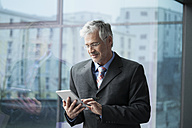 Businessman standing at window using digital tablet - RBF002664