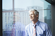 Businessman standing at window looking at distance - RBF002670