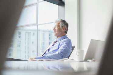 Businessman sitting at desk, looking at distance - RBF002681