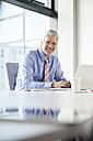 Businessman sitting at desk using laptop - RBF002684