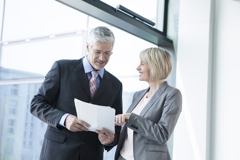 Businissman and businesswoman discussing documents - RBF002696