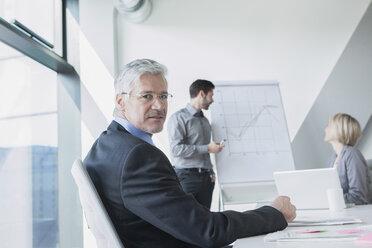 Businessman in meeting listening to presentation - RBF002707