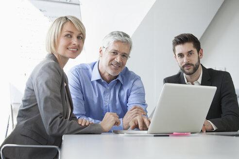 Businesspeople in informal meeting discussing new strategies - RBF002751