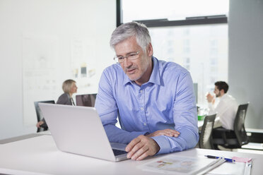 Mature businessman working in office - RBF002718