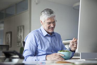 Businessman sitting at desk, eating salad - RBF002735