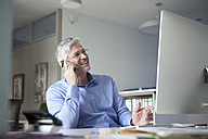 Businessman sitting at desk, talking on the phone - RBF002748