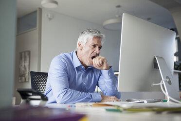 Businessman sitting at desk, yawning - RBF002739