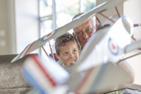 Grandfather and grandson building up a model airplane - ZEF004854