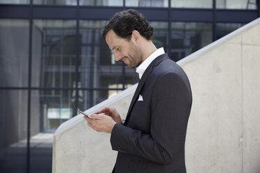 Businessman using smartphone in a modern building - FMKF001521