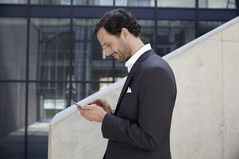 Businessman using smartphone in a modern building - FMKF001521