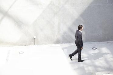 Businessman walking in a modern building - FMKF001553