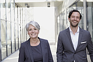 Portrait of two smiling business people - FMKF001542