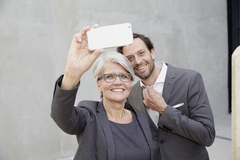 Businesswoman taking a selfie with smartphone - FMKF001545