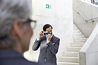 Businessman photographing his female colleague with camera - FMKF001550