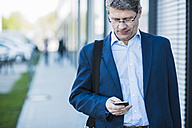 Germany, Portrait of a mature businessman in street holding smart phone - UUF004080