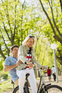 Mature couple riding bike in park, man sitting on rack - UUF004120