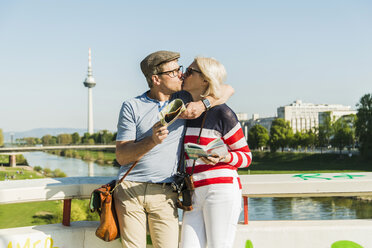 Germany, Mannheim, Mature couple taking city break, kissing on bridge - UUF004156