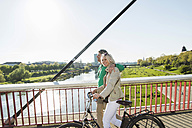 Germany, Mannheim, Mature couple crossing bridge, pushing bicycle - UUF004141