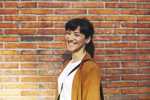 Portrait of laughing businesswoman in front of a brick wall - EBSF000608