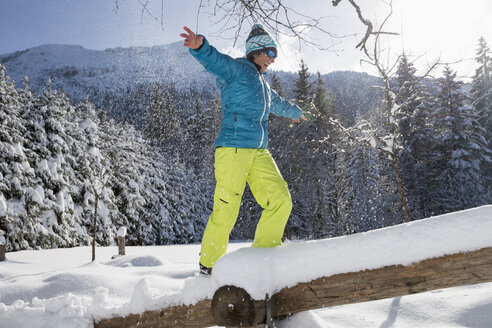 Germany, Bavaria, Inzell, woman balancing on snow-covered tree trunk - FFF001445