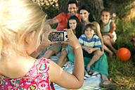 Girl taking picture of family at tree - TOYF000249