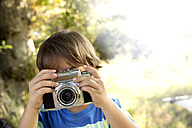 Boy with analog camera taking a picture outdoors - TOYF000252
