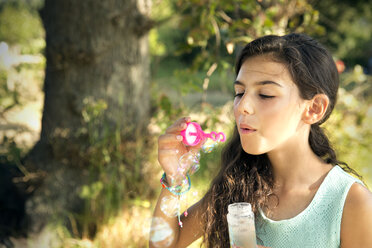 Girl blowing soap bubbles outdoors - TOYF000255