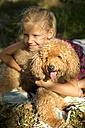 Happy girl hugging dog on blanket - TOYF000258