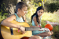 Girl in meadow playing guitar with sister watching - TOYF000261