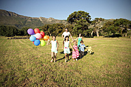 Happy family running with balloons on meadow - TOYF000264