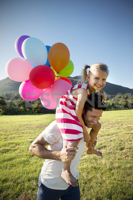 Happy father carrying daughter with balloons on shoulders - TOYF000267