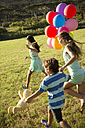 Happy children running with balloons on meadow - TOYF000270