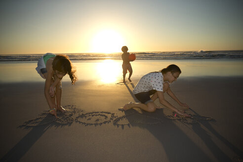 Children on the beach at sunset drawing in sand - TOYF000278