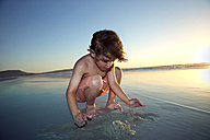 Boy playing on beach at sunset - TOYF000284