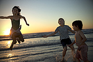 Three children playing on the beach at sunset - TOYF000286