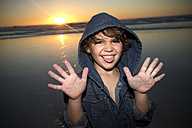 Portrait of playful boy on beach at sunset - TOYF000289