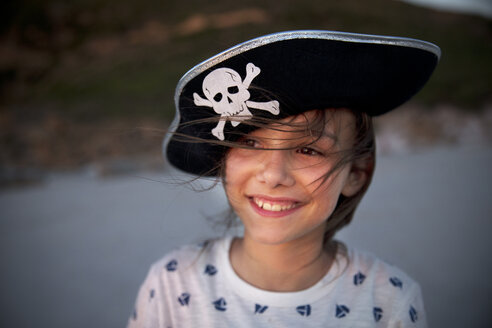 Portrait of smiling girl wearing pirate's hat on the beach - TOYF000292