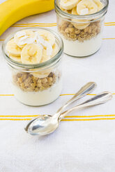 Glasses of natural yoghurt, granola, banana slices and coconut flakes - LVF003312