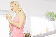 Smiling young blond woman with cup of coffee in the kitchen - MADF000234