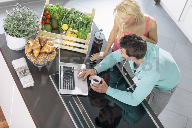 Couple using laptop in the kitchen - MADF000242