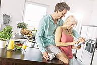 Couple using digital tablet in the kitchen - MADF000249