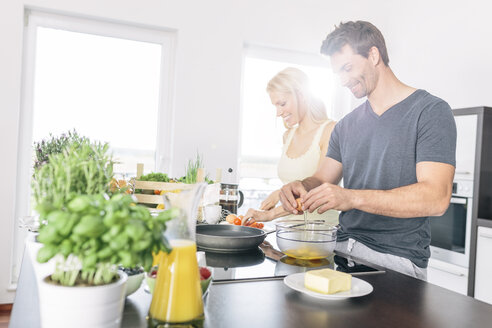 Couple preparing scrambled eggs together in the kitchen - MADF000226