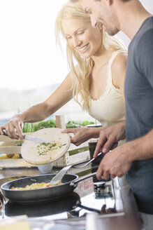 Couple preparing scrambled eggs together in the kitchen - MADF000261