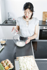 Woman pouring water in a glassbowl of flour - FLF001040
