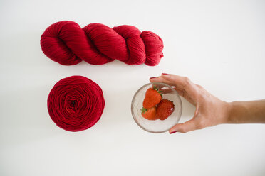 Hand dyed red yarn and woman's hand reaching for glass bowl of strawberries - FLF001129