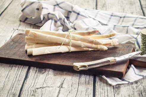 Bunch of white asparagus on wooden chopping board - SBDF001844