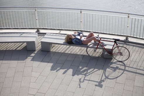 Germany, Duesseldorf, blond woman lying on a bench having a rest in front of Rhine River - RHF000817