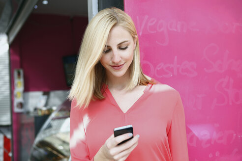 Smiling blond woman looking at her smartphone in front of a market stall - RHF000848