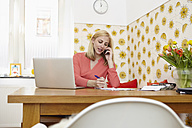 Young woman telephoning with smartphone at her home office - RHF000850