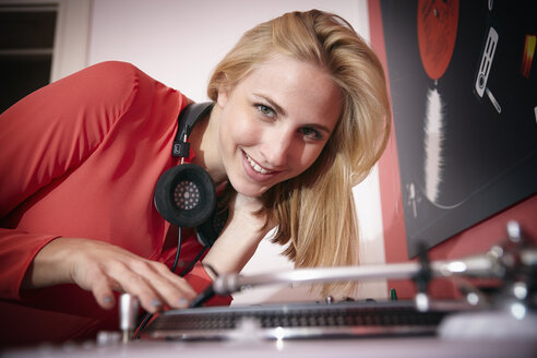 Portrait of smiling young woman with headphones and record player - RHF000856